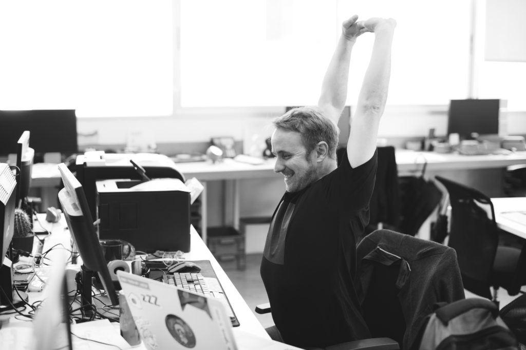 Stretching your arms up overhead is a great stretch to maintain good posture while working at your desk